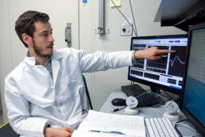 Scientist Ilya Monosov wearing a white lab coat points to a computer screen