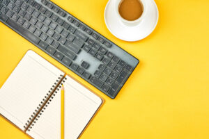 computer keyboard, cup of coffee, notebook, and pencil on yellow background